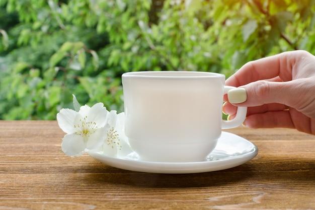 Weibliche hand mit weißer tasse tee und jasmin.