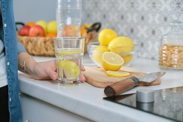 Weibliche hand mit zitronenscheibe in der küche, mit frisch gemachtem getränk sprudelwasser mit zitrone