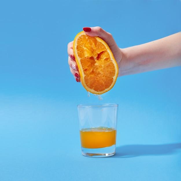 Weibliche hand quetschen orange auf einem farbigen hintergrund