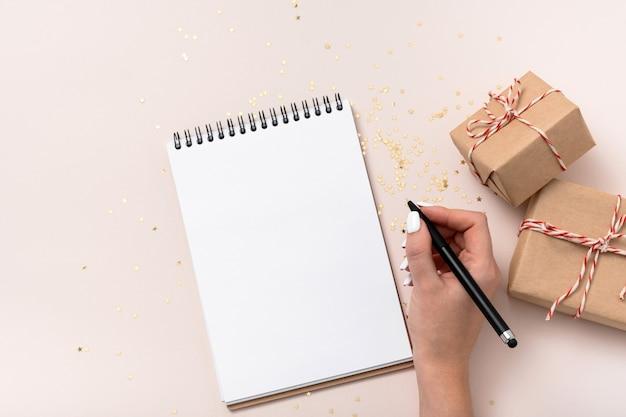 Weibliche hand schreiben halten notizbuch leeres papiermodell, goldene sterne konfetti, geschenkboxen auf beigem hintergrund. flache lage, draufsicht, kopierraum, minimalistisch. weihnachten zusammensetzung des neuen jahres.