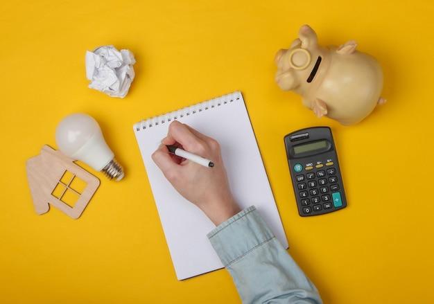 Weibliche hand schreiben in notizbuch auf gelb. wirtschaftliche berechnung der wohnkosten.