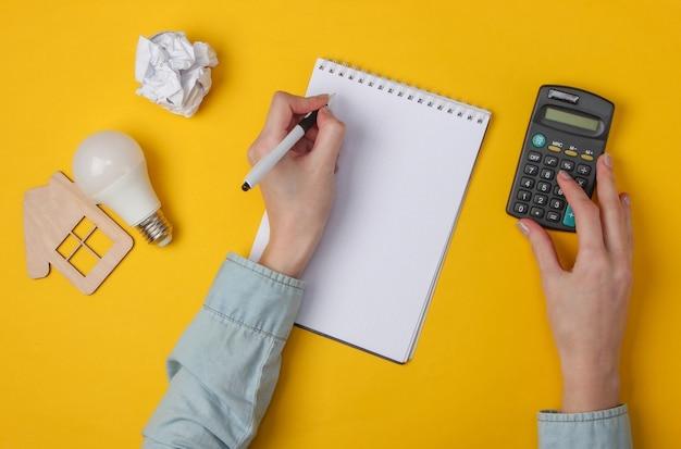 Weibliche hand schreiben in notizbuch und verwenden taschenrechner auf gelb