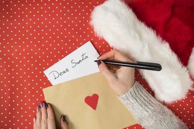 Weibliche hand schreibt brief an santa, umschlag. weihnachtsmütze, rote oberfläche.