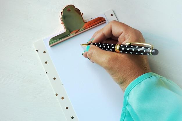 Weibliche hand schreibt mit einem kugelschreiber auf ein leeres blatt papier auf einem klemmbrett.
