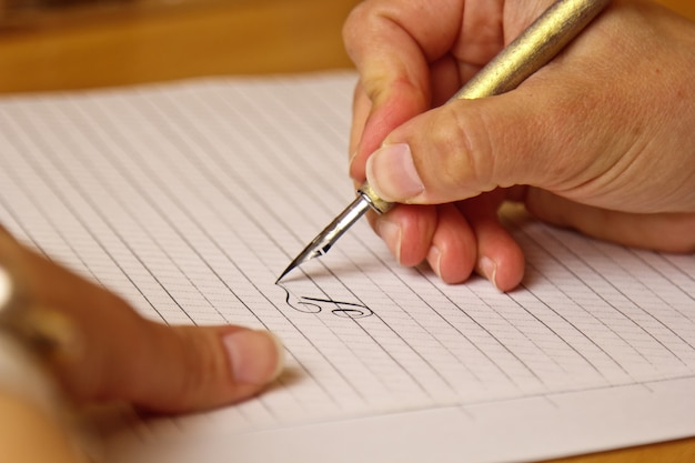 Weibliche hand schreibt mit einem tintenstift auf ein weißbuchblatt mit streifen.