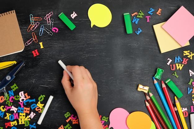 Weibliche hand schreibt mit weißer kreide auf eine tafel