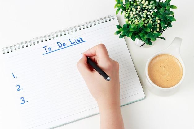 Weibliche hand schreibt, um liste im notizbuch zu tun, das copyspace und plant