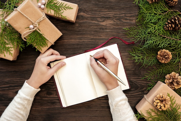Weibliche hand schreibt weihnachtsbrief in notizbuch auf dunklen brettern mit geschenken und tannenzapfen