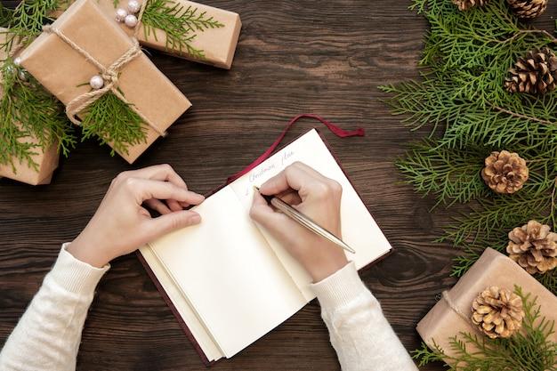 Weibliche hand schreibt weihnachtsplan in notizbuch auf dunklen brettern mit geschenken und tannenzapfen