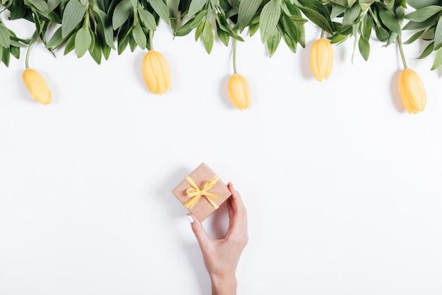 Weibliche hand setzt ein kästchen mit einem geschenk auf den tisch mit gelben tulpen