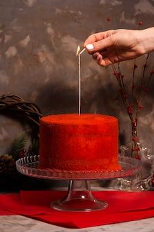 Weibliche hand setzt feuer auf eine wunderkerze, die auf einem schönen roten samtgeburtstagskuchen brennt