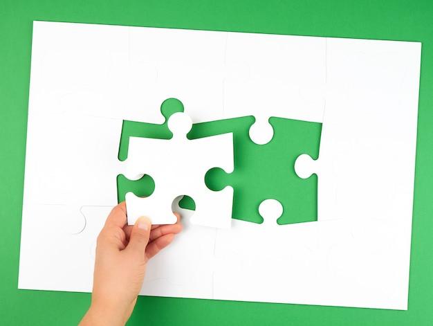 Weibliche hand setzt leere weiße große puzzlespiele auf grün