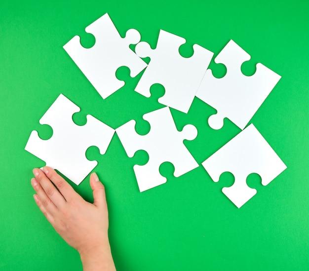 Weibliche hand setzt leere weiße große puzzlespiele