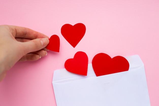 Weibliche hand setzt rote papierherzen in einen weißen umschlag ein. liebesnachricht. valentinstag-konzept.