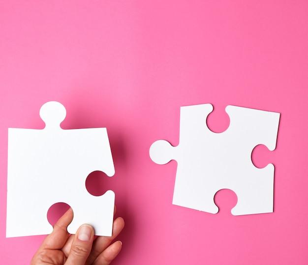 Weibliche hand setzt weiße große puzzlespiele auf einen rosa hintergrund
