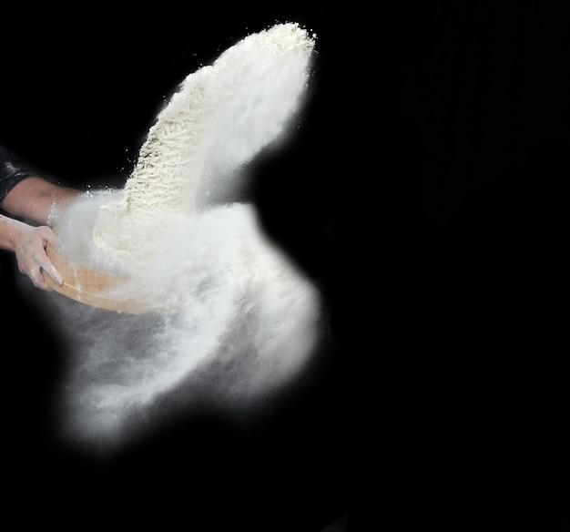 Weibliche hand siebt weißes weizenmehl durch ein rundes holzsieb