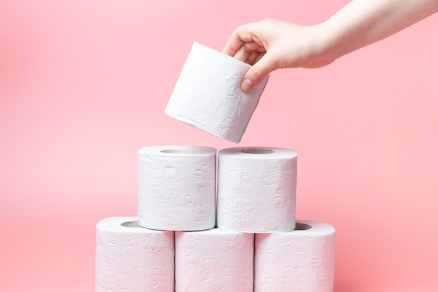 Weibliche hand stapelt toilettenpapier in einem stapel auf rosa hintergrundnahaufnahme.