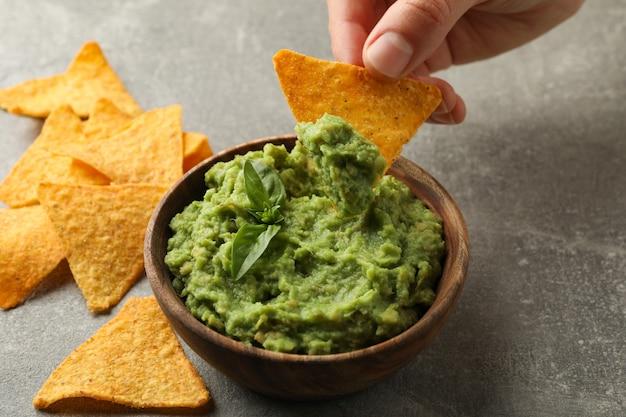 Weibliche hand taucht chips scheibe in guacamole, nahaufnahme