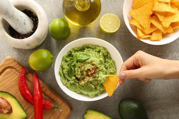 Weibliche hand taucht chipsscheibe in guacamole, draufsicht ein