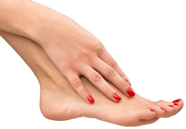 Weibliche hand und fuß mit roter maniküre isoliert
