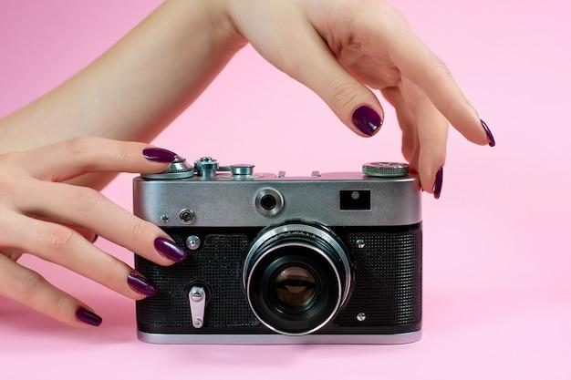 Weibliche hand und kamera auf rosa hintergrund