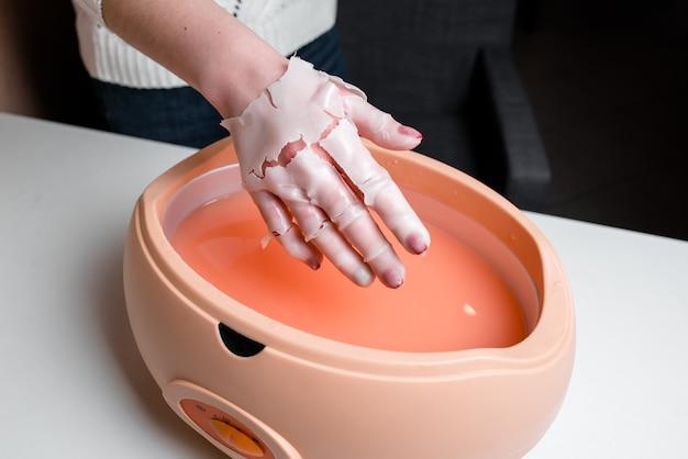 Weibliche hand und orange paraffinwachs in der schüssel. maniküre und hautpflege.