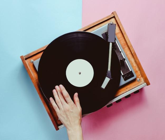 Weibliche hand verwendet vinyl-player, konzeptionelles foto, dj, minimalismus, draufsicht