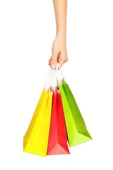 Weibliche hand, welche die einkaufstaschen, lokalisiert hält