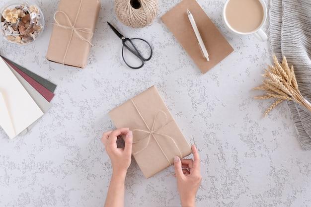 Weibliche hand wickelt eine geschenkbox mit einem kraftpapier auf weißer strukturierter tabelle, draufsicht und ebenenlage ein