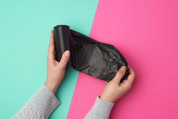 Weibliche hand wickelt eine schwarze plastiktüte für müll ab