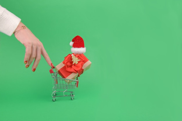 Weibliche hand ziehen einen einkaufswagen des einkaufswagens mit weihnachtsgeschenkbox, der weihnachtsmannmütze auf einem grünen hintergrund trägt