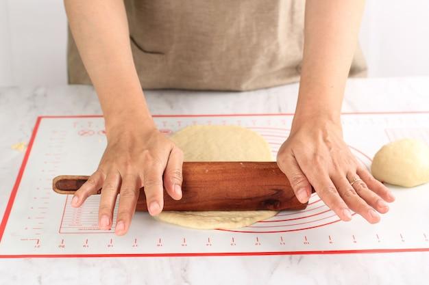 Weibliche handgerollte pizza oder brotteig mit einem nudelholz auf einem weißen tisch, bestreut mit mehl. schritt für schritt in der küche backen