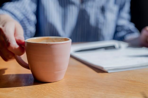 Weibliche handnahaufnahme, die kaffeetasse im café mit unscharfem notizbuch und stift auf hintergrund nimmt