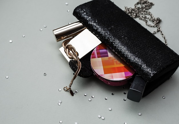 Weibliche handtasche mit kosmetik über grauem hintergrund