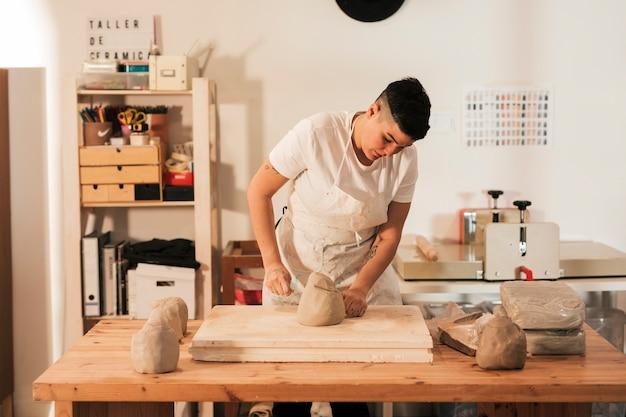 Weibliche handwerkerin, die auf dem tisch einen gekneteten lehm mit thread schneidet