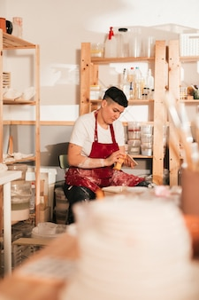 Weibliche handwerkerin, welche die keramikfliesen mit schwamm säubert