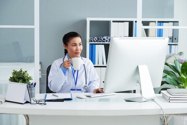 Weibliche hausärztin trinkt eine tasse kaffee und checkt e-mails von patienten und kollegen ...