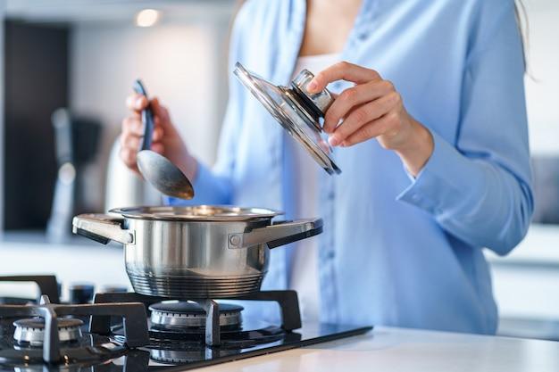 Weibliche hausfrau, die stahlmetall-topf für die zubereitung des abendessens in der küche zu hause verwendet. küchenutensilien zum kochen