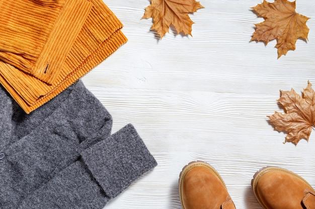 Weibliche herbstkleidung, modische orangefarbene lederstiefel, warmer strickpullover und helle hosen, dekoriert herbstliche blätter aus ahorn