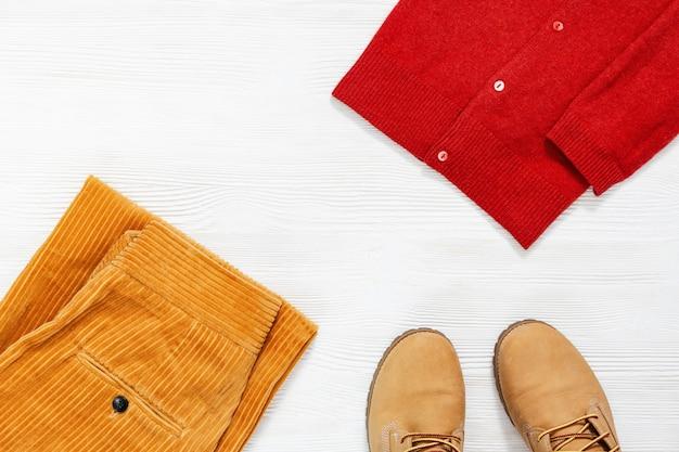 Weibliche herbstkleidung, modische orangefarbene lederstiefel, warmer strickpullover und helle hosen.
