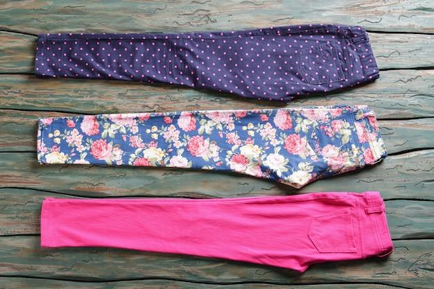 Weibliche hosen in verschiedenen farben. hellrosa und dunkelblaue hose. auswahl an hosen im shop. vielzahl von mustern.