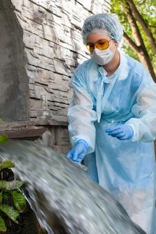 Weibliche hygieneinspektorin oder epidemiologin entnimmt eine wasserprobe aus kommunalem abwasser
