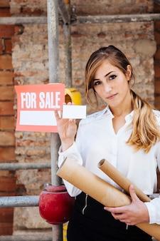 Weibliche immobilienmakler zeigt visitenkarte