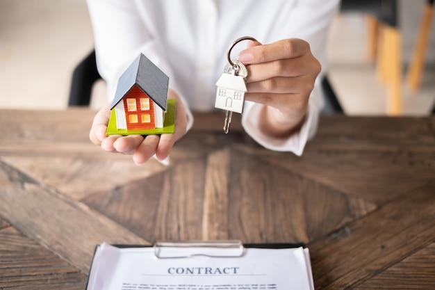 Weibliche immobilienmaklerhand, die hausmodell und hausschlüssel mit vertrag auf tabelle hält