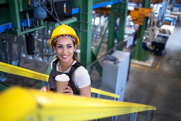 Weibliche industriearbeiterin in uniform und helm, die die geländer hält und werkstreppen steigt.