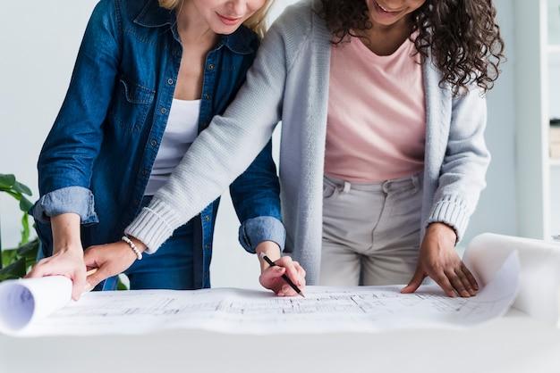 Weibliche ingenieure, die zusammen an grundriss arbeiten