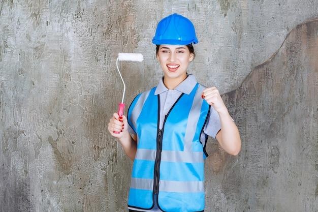 Weibliche ingenieurin in blauer uniform und helm hält eine trimmrolle zum malen und zeigt positives handzeichen.
