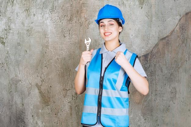 Weibliche ingenieurin in blauer uniform und helm hält einen metallschlüssel und zeigt positives handzeichen.