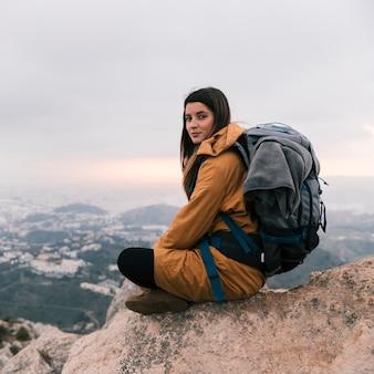 Weibliche junge frau, die am rand des berges mit ihrem rucksack sitzt