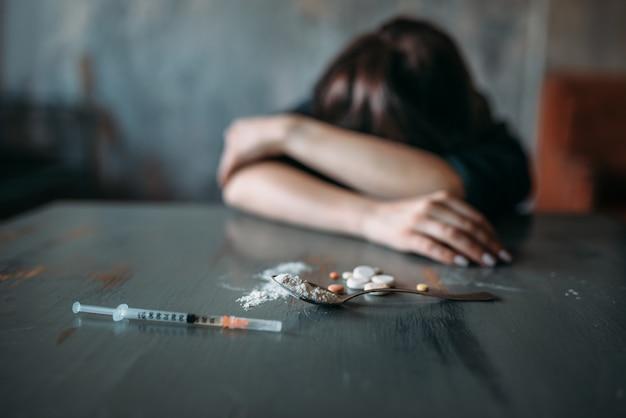 Weibliche junkie-hand, die nach der dosis greift
